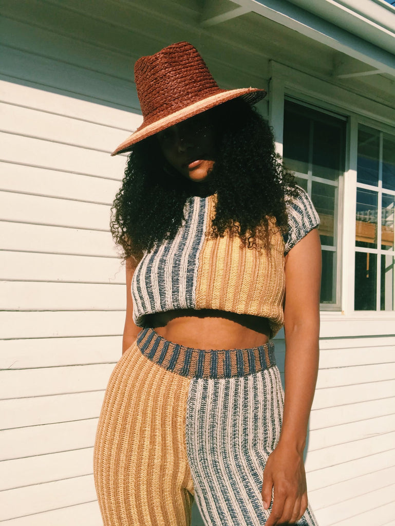 Model wears a brown wide brim hat with a matching two tone yellow and blue striped knit set.