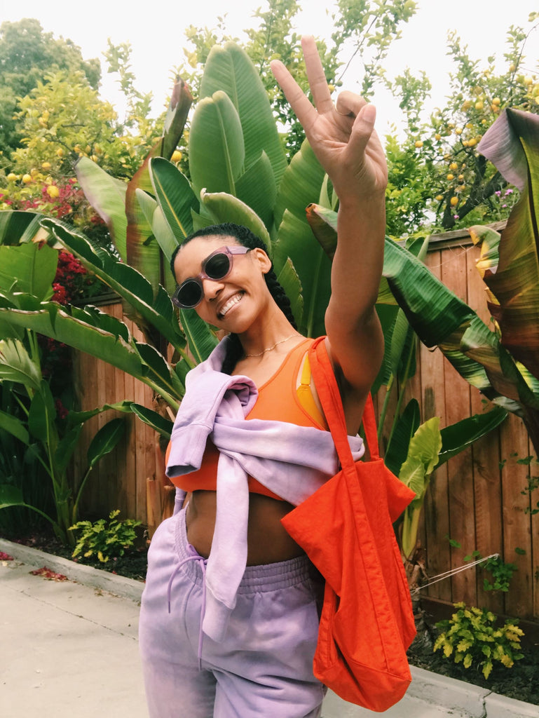 Model stands before green foliage wearing a light purple sweatsuit. The top is tied around her chest over an orange sports bra, and she wears an orange tote bag. She is smiling, wearing sunglasses, and has her left hand holding up a peace sign.