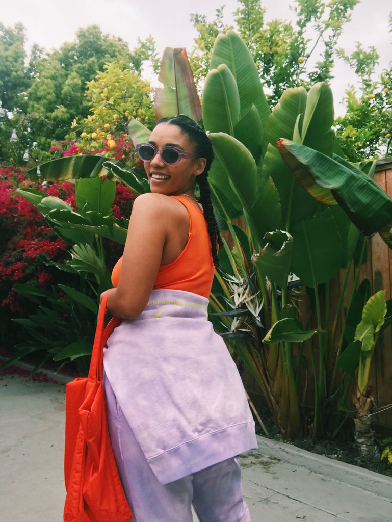 Model stands before green foliage wearing a light purple sweatsuit. The top is tied around her waist over an orange sports bra, and she holds an orange tote bag. She is smiling, wearing sunglasses, and looking over her shoulder.