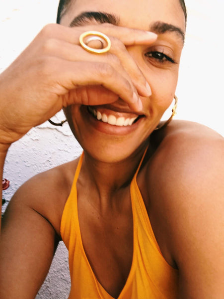 Close up of Courtney wearing an orange halter top and gold jewelry.