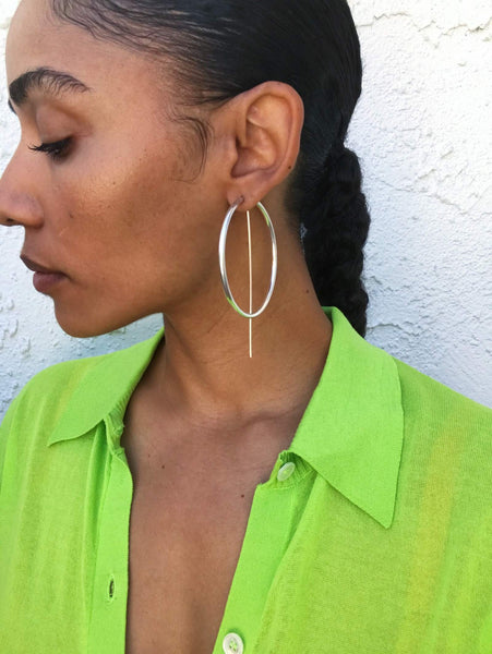 Close up of Courtney wearing a green carigdan top and silver earrings.