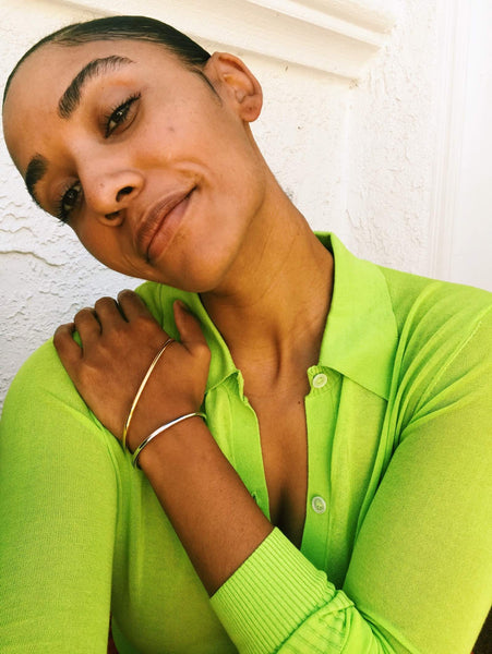 Close up of Courtney wearing an green cardigan top and two tone bracelet.