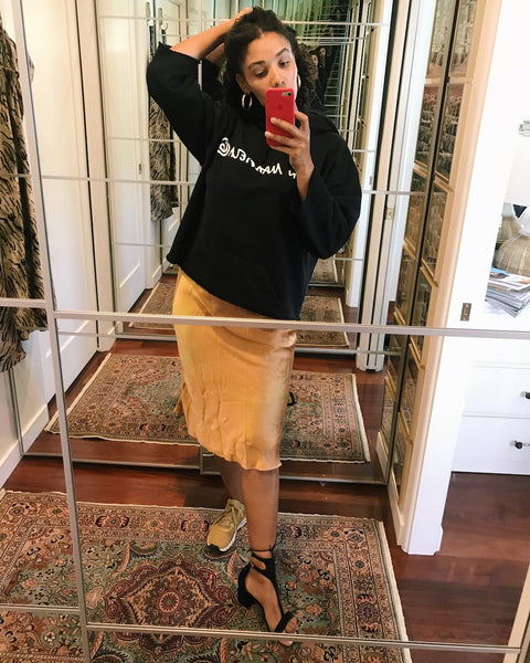 Courtney takes a mirror selfie wearing a black cropped hoodie over a nude slip dress.