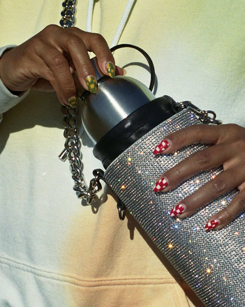 A detail photo of Evelynn's hands holding a rhinestone water bottle holder from Kara, and pulling a stainless steel bottle out.