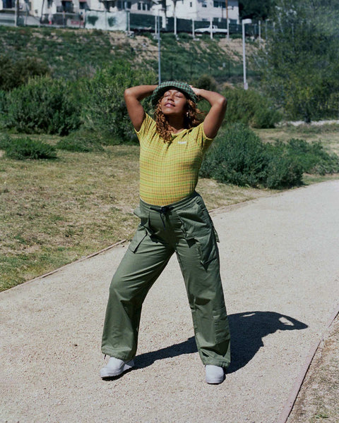 Evelynn standing on a dirt path in a park, holding her hands up behind her head, wearing a yellow check shirt by Stussy and military green pants by Perks and Mini.
