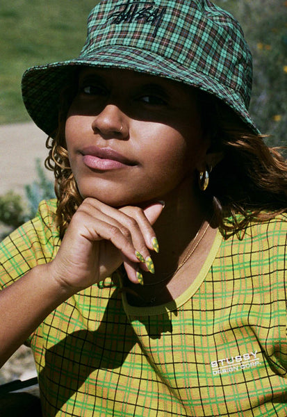 A portrait photo of Evelynn, wearing a green plaid hat and yellow checked t-shirt by Stussy, with her chin resting on her hand.