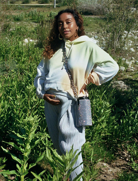 A photo of Evelynn standing amongst grass and greenery, wearing a the-die Collina Strada Sweatshirt, grey Pleats Please pants, and a Kara rhinestone water bottle holder, with her hand under her pregnant belly.