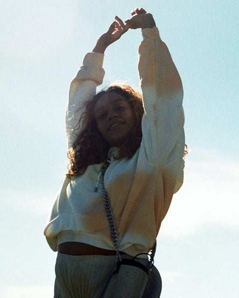 A photo of Evelynn against the sky, shot from waist up, with her arms in the air, smiling.