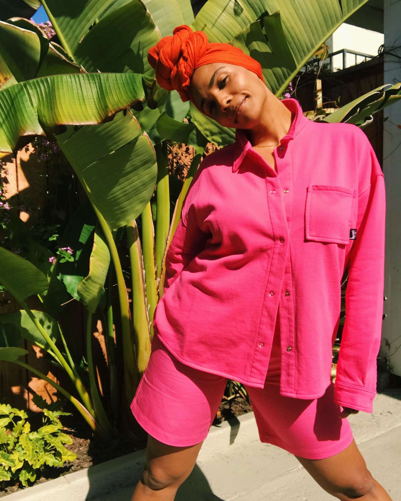 Courtney standing in front of a large outdoor plant, wearing a hot pink button front shirt and matching shorts by Stussy.