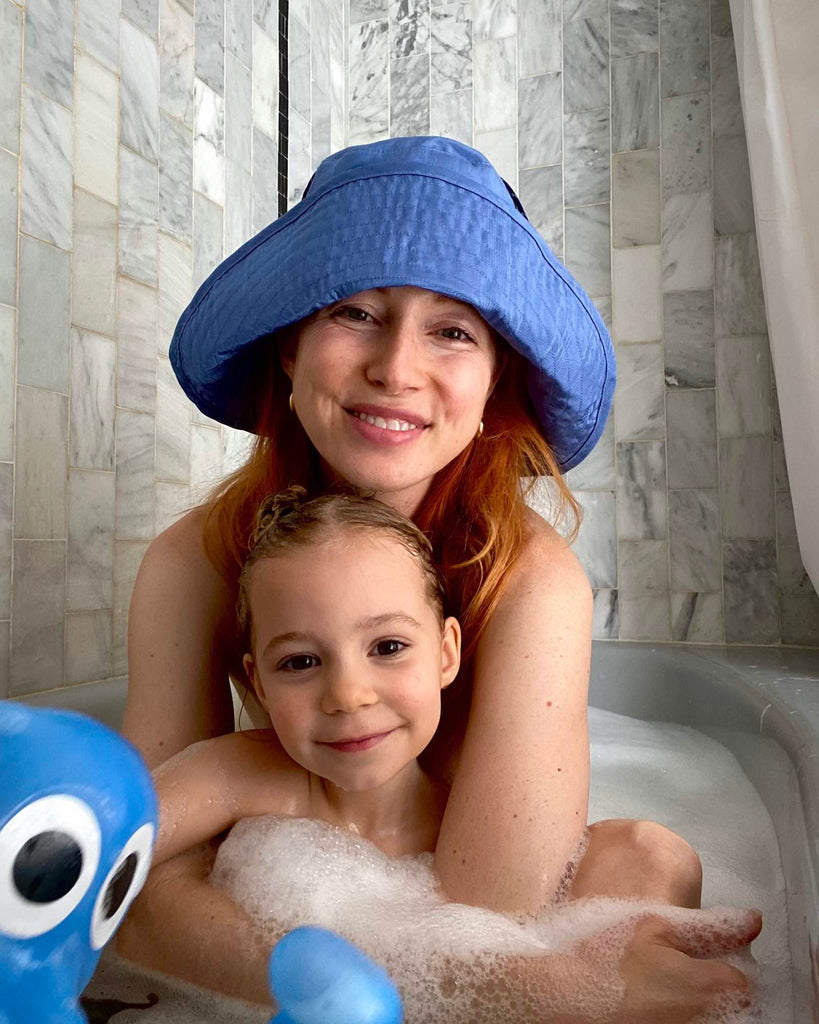 Tiff, wearing a blue hat by Kkco, and Beanie, her daughter, sit in the bath smiling.