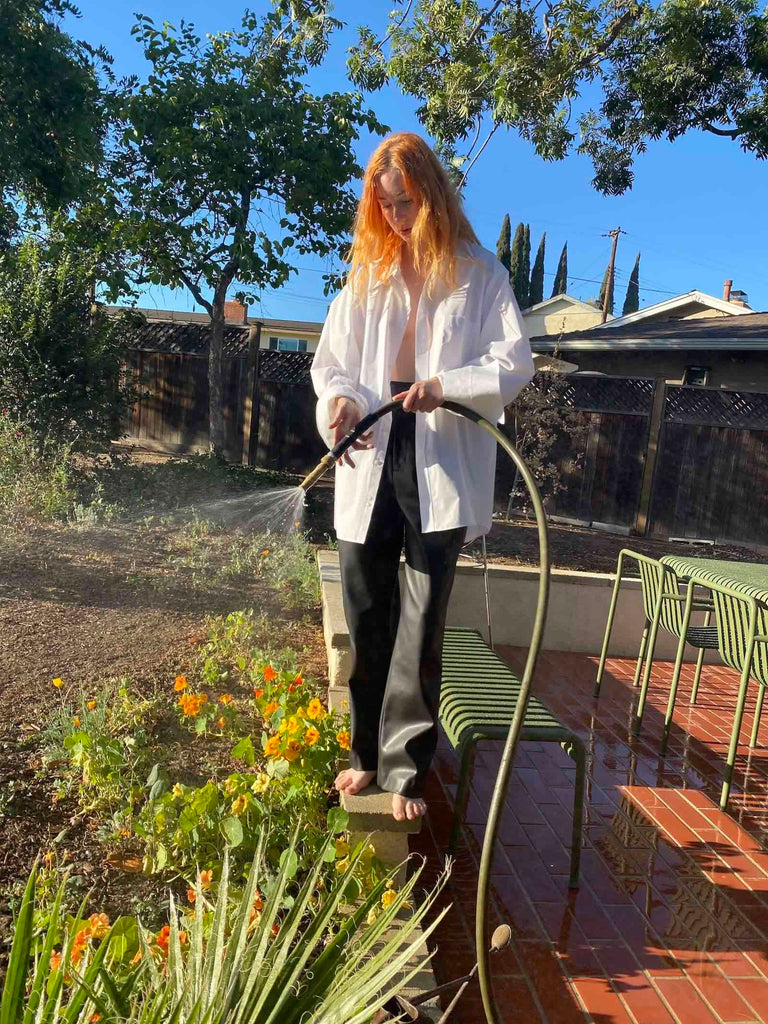 Photo of a red-haired woman wearing black leather trousers and a white button up standing and using a hose to water plants.