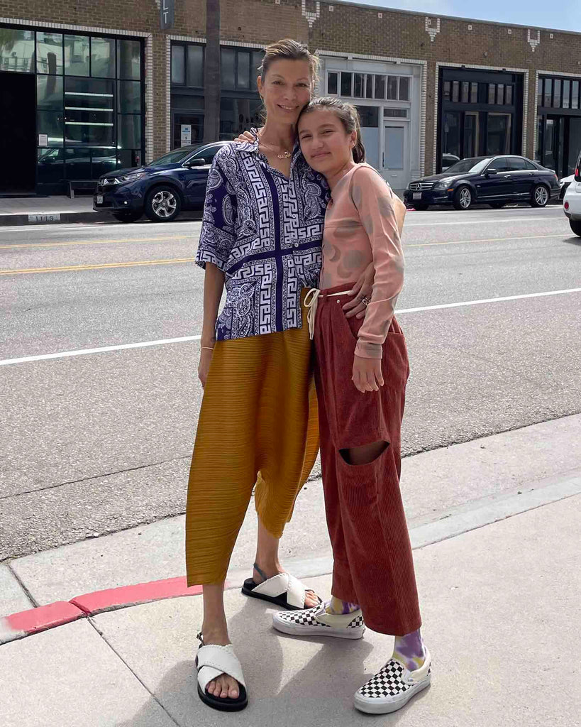 Mother and daughter stand on the sidewalk.