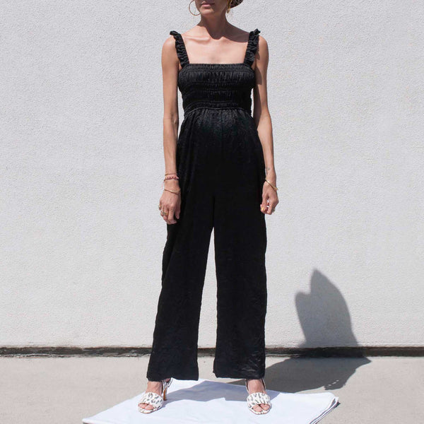 GANNI - Crinkled Satin Jumpsuit, a black scrappy jumpsuit with ruched bodice.