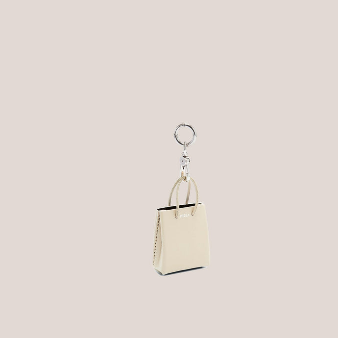 Medea - Mini Prima Bag Keychain in Ivory, angled view, available at LCD.