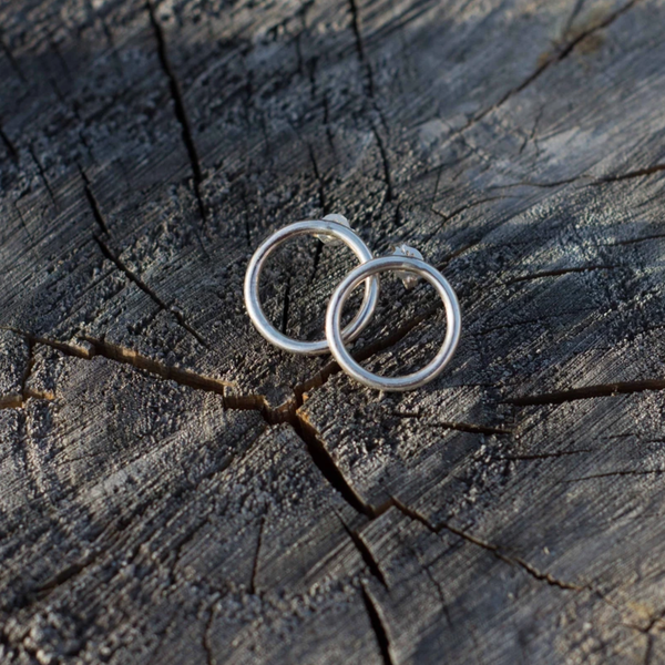 Silver circle ring stud earrings on wood backdrop