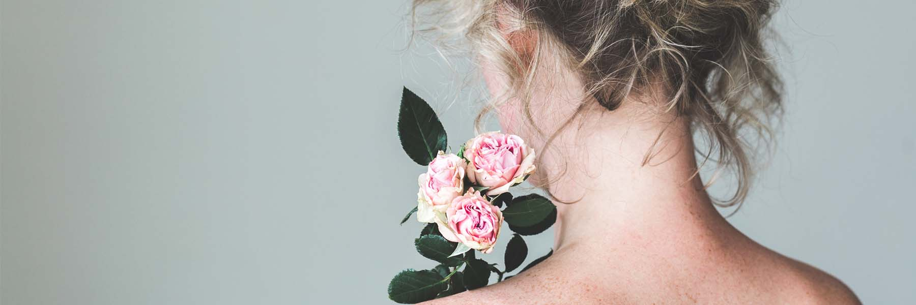 back view of womans neck and holding pink roses