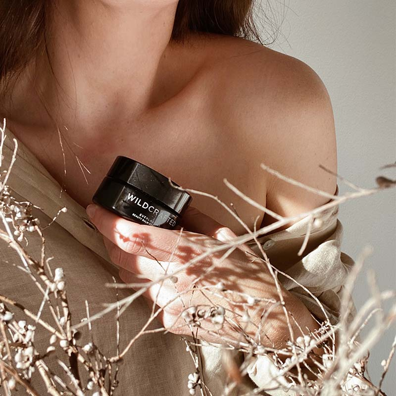 Woman with bare shoulder holding Wildcrafted makeup pot