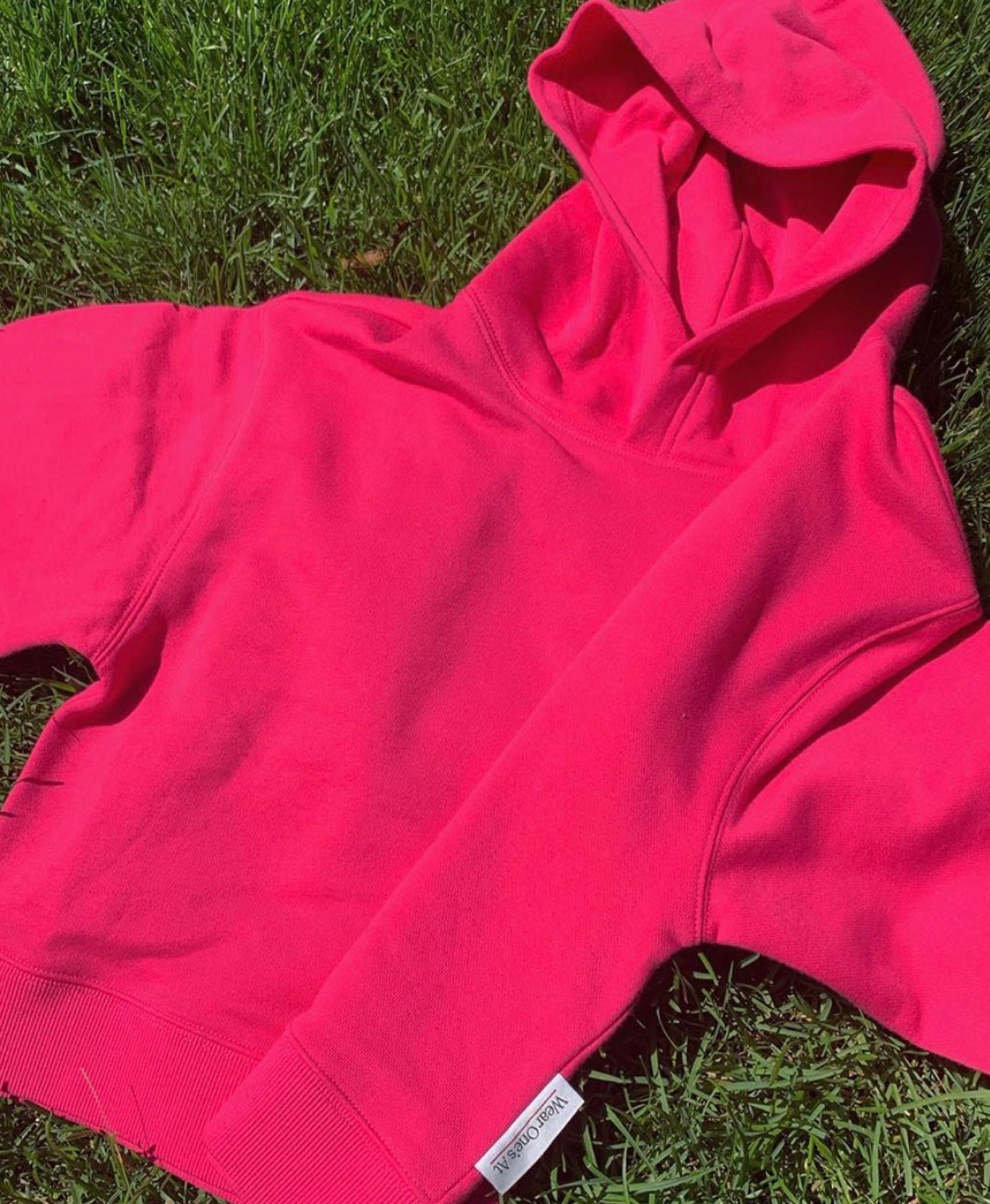 Wear One's At French Terry Cropped Hoodie in Watermelon Laying on Grass Front View