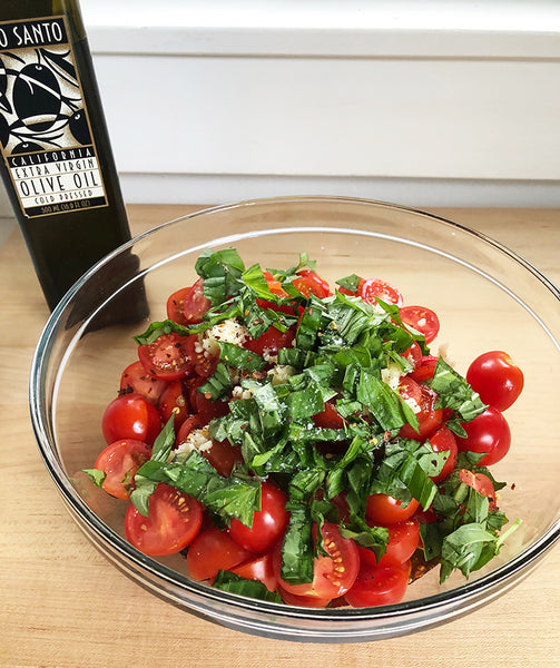 Tomatoes for Ina's Garden Summer Pasta macerating in our Glass Nesting Bowl on a counter next to a bottle of Olio Santo Olive oil.