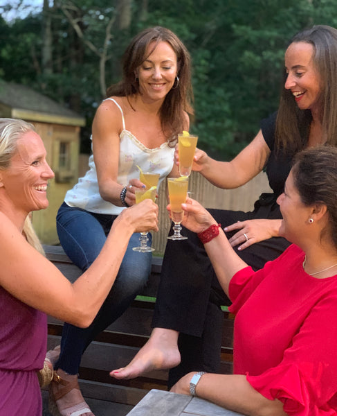 group of women enjoying cocktails outdoors on a deck