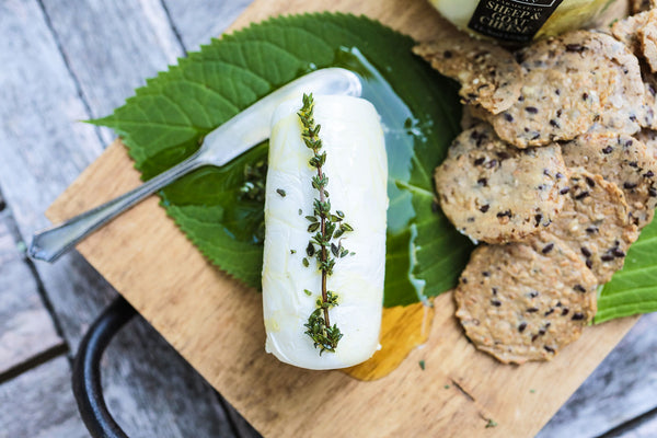 Goat Cheese on a Feating Board with rosemary and crackers