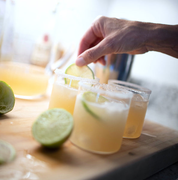 Adding a lime to each cocktail glass