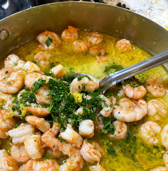 Shrimp in a pot with butter, garlic, and parsley