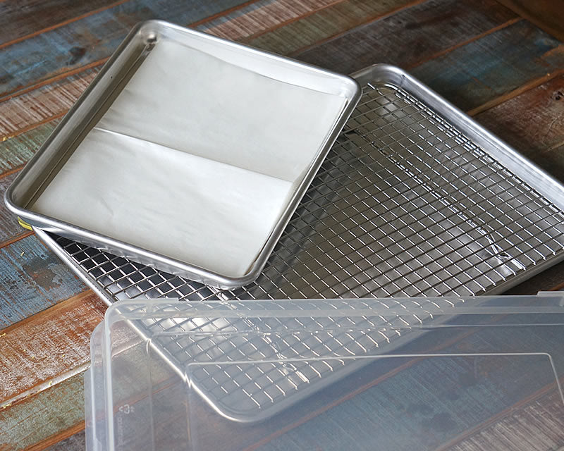 A half sheet pan with the cross wire cooling rack, a quarter sheet pan lined with a Parchment Baking Sheet and a half sheet pan cover on a wood table.
