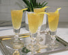 4 La Rochere Antoine Champagne Flutes with yellow cocktail garnished with lemon on a silver tray