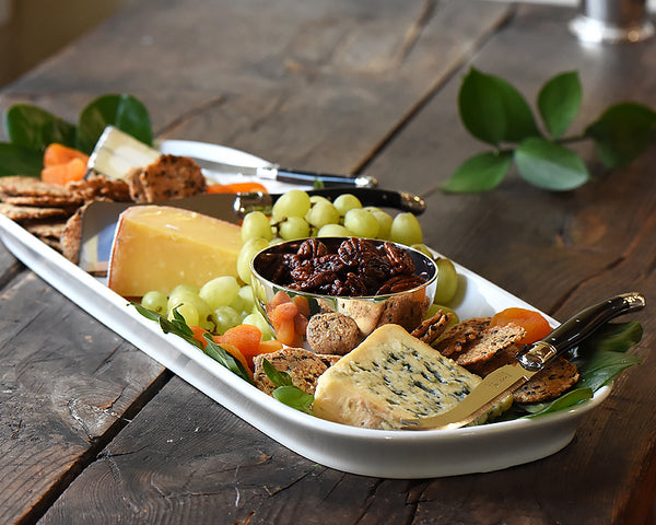 The Barn Platter sits on a wood table and is filled with cheeses, green grapes and earthy crackers