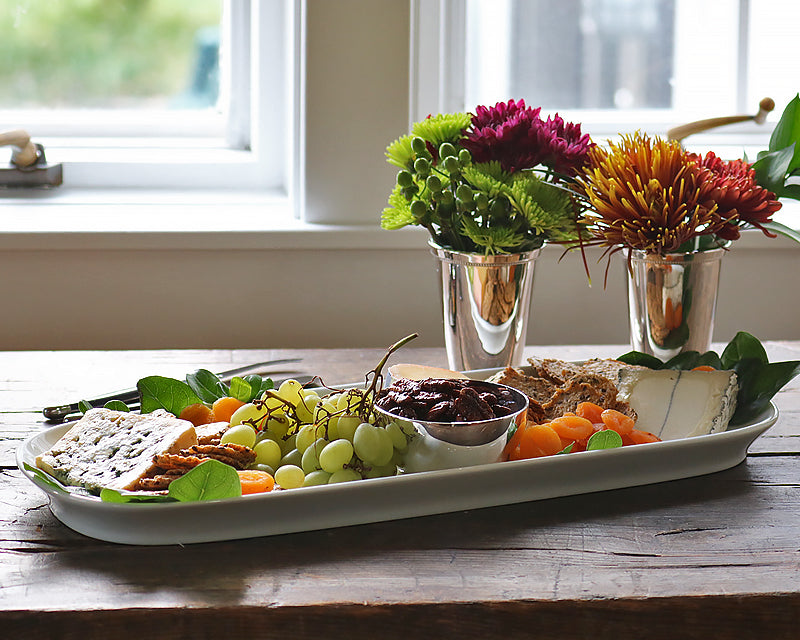 The Barn Platter sits on a wood table next to Hotel Silver mint julep cups filled with fall flowers