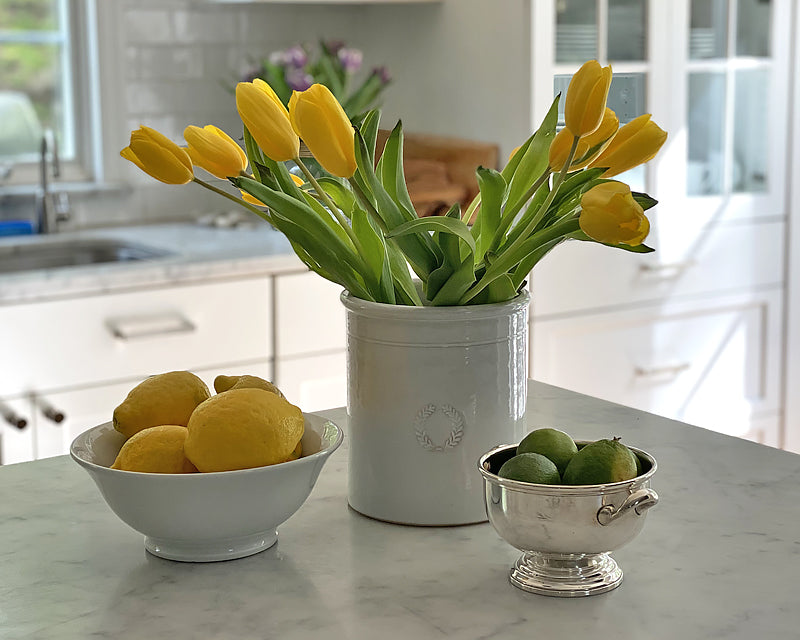 Classic Footed Bowl filled with lemons on a marble counter. A great bowl for keeping fruit handy on the counter.