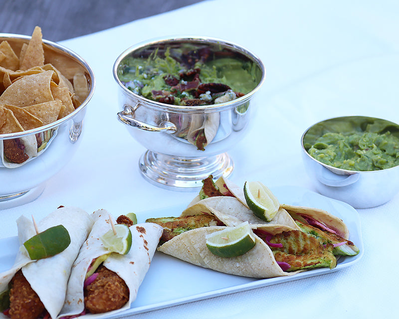 Simple take-out tacos served on the Narrow Platter surrounded by Hotel Silver Bowls filled with tortilla chops and guacamole.