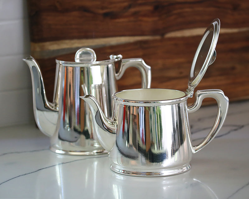 Vintage HÔTEL Silver Tea & Coffee Pots sit on a counter with open lids.  They were made for the British Ministry of Defense and used in their officers' messes.