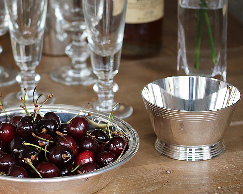 HÔTEL Silver Deco Bar Bowl on a farm table next to the HÔTEL Silver Round Dish filled with cherries.