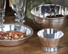 HÔTEL Silver Deco Bar Bowl on a farm table next to the HÔTEL Silver Round Dish filled with assorted nuts.