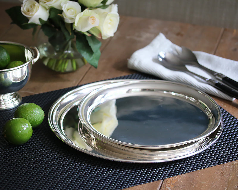 Hotel Silver round trays displayed on a black basketweave placemat next to our Hotel Silver footed bowl filled with limes.