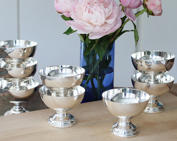 HÔTEL Silver Sorbet Bowls stacked on a  wood board next to a glass filled with pink peonies