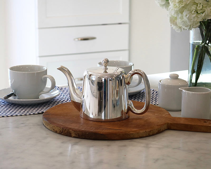HÔTEL Silver Teapot on kitchen counter with tea cups