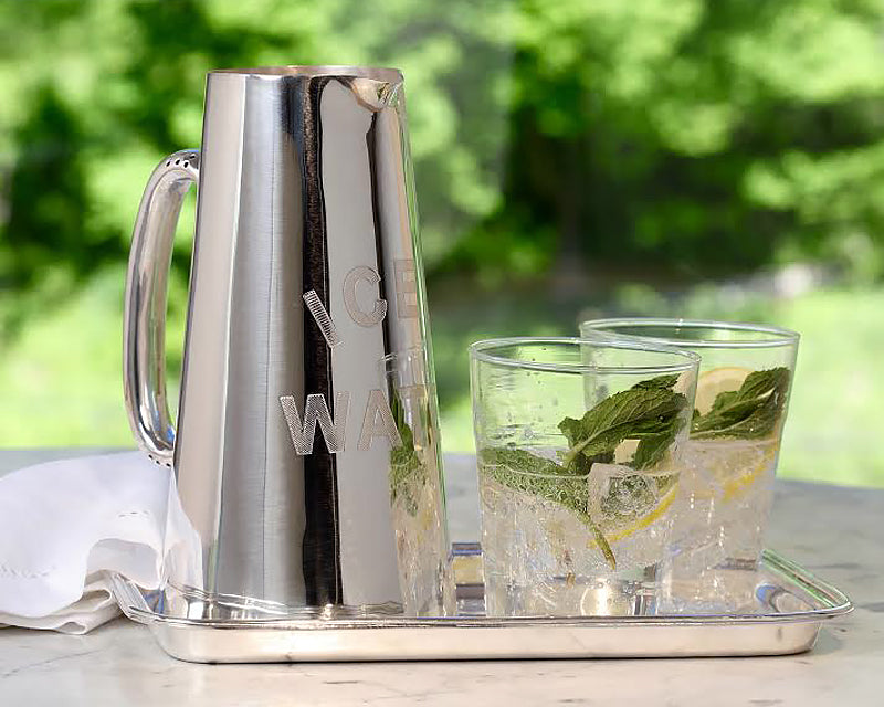 HÔTEL Silver Water Pitcher on top of a matching silver drink tray