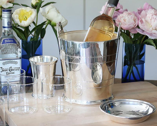 Hotel Silver Wine cooler on a bar table filled with simple clear glassware and beautiful floral arrangements.