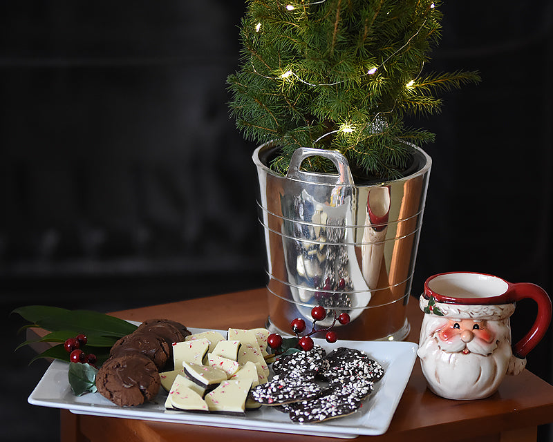 Silver ice bucket holding a Christmas tree decoration displayed next to a platter of holiday treats and a Santa mug.
