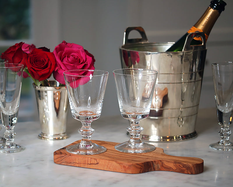 La Rochere Antonie glasses on a cutting board next to a HÔTEL silver wine cooler and HÔTEL silver mint julip cup.