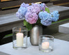 Clear glass hurricanes make a statement next to a vase filled with summer hydrangeas.