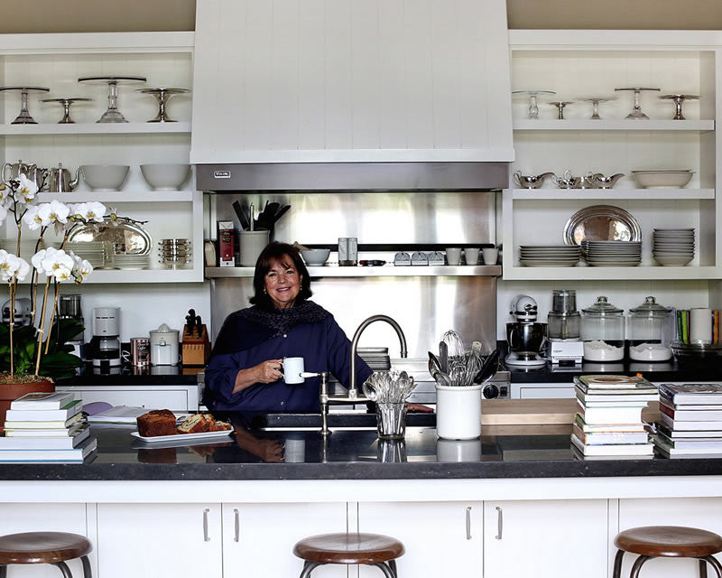 Ina Garten in her kitchen with Detailed image of HÔTEL Silver pieces behind her on shelves. Image: Béatrice de Géa for The New York Times