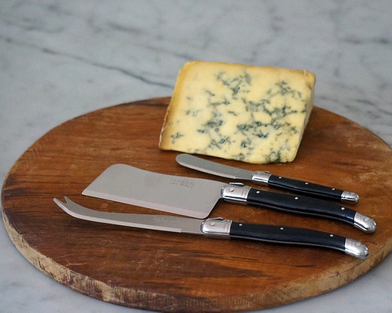 Black handled Laguiole cheese knife set on cutting board next to slab of cheese