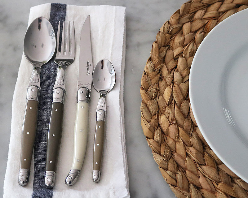 Flatware utensils on a napkin next to a Pillivuyt dinner plate