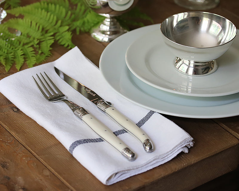 French knife and fork on a napkin next to a table setting
