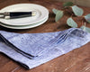 casually folded indigo linen napkin next to white dinnerware plate and everyday flatware
