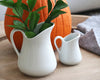 A fall setting with the milk jugs sitting side by side near a big orange pumpkin